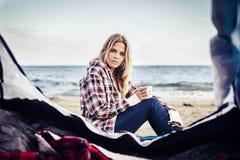 Nette blonde Dame, die sich außerhalb eines Zeltes nahe den Wellen hinsetzt Lizenzfreie Stockfotografie