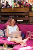 Nette blonde Entspannung mit Laptop auf Couch. Lizenzfreie Stockfotografie