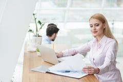 Nette blonde Frau arbeitet im Büro Stockbild