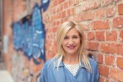 Nette blonde Frau, die auf Backsteinmauer sich lehnt Lizenzfreie Stockfotografie
