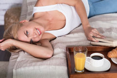 Nette blonde Frau, die auf Bett mit Buch liegt Stockbilder