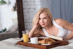 Nette blonde Frau, die auf Bett mit Buch liegt Stockbild