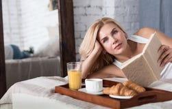 Nette blonde Frau, die auf Bett mit Buch liegt Lizenzfreie Stockfotografie