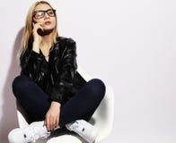 Nette blonde Frau, die auf dem Stuhl und dem Gebrauch martphone ove sitzt Lizenzfreie Stockfotografie