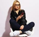 Nette blonde Frau, die auf dem Stuhl und dem Gebrauch Smartphone sitzt Stockbilder