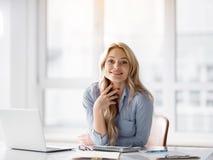 Nette blonde Frau, die am Desktop arbeitet Stockfoto