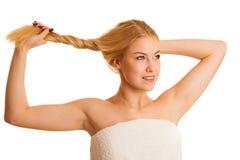 Nette blonde Frau, die ihr ahir als Begriffsfoto für starkes hält Stockfoto