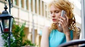 Nette blonde Frau, die im Café sitzt und am Telefon spricht Lizenzfreies Stockfoto