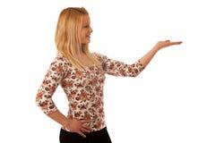 Nette blonde Frau, die in Kopienraum zeigt, wie sie eine PR zeigt Lizenzfreie Stockfotos