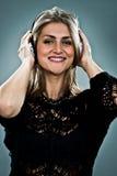 Nette blonde Frau, die Musik hört Lizenzfreies Stockfoto