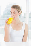 Nette blonde Frau, die Orangensaft trinkt Lizenzfreie Stockbilder