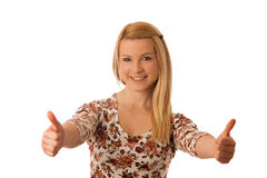 Nette blonde Frau, die sich Daumen als Geste für Erfolg isola zeigt Lizenzfreie Stockbilder