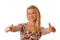 Nette blonde Frau, die sich Daumen als Geste für Erfolg isola zeigt Stockbilder