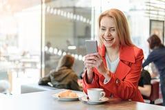 Nette blonde Frau, die Smartphone in der Cafeteria verwendet Lizenzfreies Stockbild