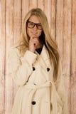Nette blonde Frau, die tragende Gläser des Kinns und weißen Mantel hält Stockfoto