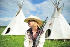 Nette blonde Frau in einem Cowboyhut, der draußen sitzt Stockfoto