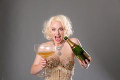 Nette blonde Frau feiert mit enormem Glas Champagner = Grau Lizenzfreie Stockbilder