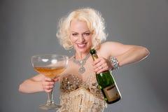 Nette blonde Frau feiert mit enormem Glas Champagner = Grau Stockbild