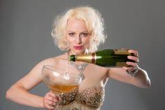 Nette blonde Frau feiert mit enormem Glas Champagner = Grau Stockbilder