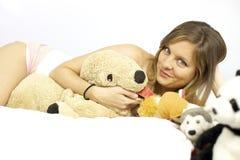 Nette blonde Frau im Bett, das mit vielen angefüllten Spielwaren legt Lizenzfreie Stockfotos