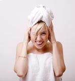 Nette blonde Frau im weißen Tuch auf ihrem Kopf, nach Badekurort- oder Badezimmeremotionalem lokalisiert Lizenzfreie Stockfotografie