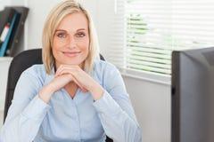 Nette blonde Frau mit dem Kinn auf ihren Händen Lizenzfreie Stockfotos