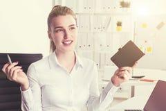 Nette blonde Frau mit dem Notizbuch, getont Stockfoto
