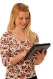 Nette blonde Frau mit dem Tablet-Computer lokalisiert über weißem backgr Stockfotografie