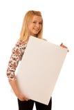 Nette blonde Frau mit der leeren weißen Fahne lokalisiert über weißem BAC Lizenzfreies Stockbild
