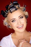 Nette blonde Frau mit ihrem Haar in den Lockenwicklern Stockfotos