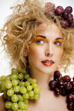 Nette blonde Frau mit kreativem bilden und Trauben Stockfoto