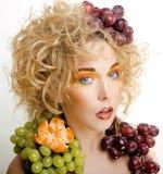 Nette blonde Frau mit kreativem bilden und Trauben Stockfotografie