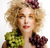 Nette blonde Frau mit kreativem bilden und Trauben Stockbilder