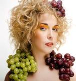 Nette blonde Frau mit kreativem bilden und Trauben Stockfotos
