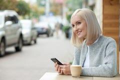 Nette blonde Frau mit Telefon im Café Stockfotografie