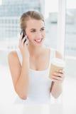 Nette blonde Frau am Telefon, das Kaffee hält Lizenzfreie Stockfotos