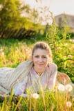 Nette blonde Frau von mittlerem Alter, die draußen auf Wiese in Co legt Stockbild