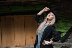 Nette blonde jugendlich Abnutzungsschwarzjacke und -hut Stockbilder