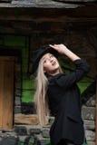 Nette blonde jugendlich Abnutzungsschwarzjacke und -hut Lizenzfreies Stockfoto