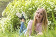 Nette blonde Jugendliche, die an einem sonnigen Tag auf dem Gras träumt Stockbild