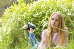 Nette blonde Jugendliche, die an einem sonnigen Tag auf dem Gras träumt Lizenzfreie Stockfotografie