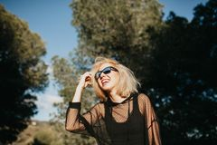 Nette blonde junge Frau in der Sonnenbrille draußen lachend in der Natur Lizenzfreie Stockfotos