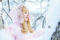 Nette blonde junge Frau, die eine rosa Jacke mit einer Haube im Winter trägt Stockfotos