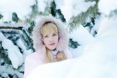 Nette blonde junge Frau, die eine rosa Jacke mit einer Haube im Winter trägt Stockfoto