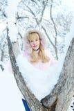 Nette blonde junge Frau hat einen Rest im Winter Stockfotografie
