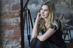 Nette blonde kaukasische Frau, die im modischen Minimum des Dachbodenschmutzes sitzt Lizenzfreie Stockbilder