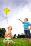 Nette blonde Kinder, die draußen spielen Lizenzfreie Stockfotos