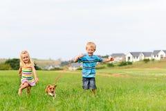 Nette blonde Kinder, die in ein Feld laufen Lizenzfreies Stockfoto