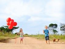 Nette blonde Kinder draußen in der Sonne Lizenzfreie Stockbilder
