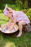 Nette blonde Kindermädchenspiele spielen Wäsche im Sommergarten Lizenzfreie Stockbilder